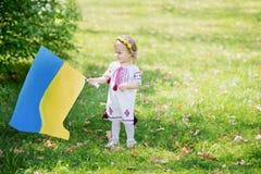 L'enfant porte le flottement drapeau bleu et jaune de l'Ukraine dans le domaine Jour de la D?claration d'Ind?pendance du ` s de l photographie stock