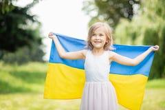 L'enfant porte le flottement drapeau bleu et jaune de l'Ukraine dans le domaine Jour de la D?claration d'Ind?pendance du ` s de l photo stock