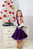 L'enfant près de la prise d'arbre de Noël patine cadeau Peu cadeau satisfaisant de Noël de fille Le meilleur cadeau jamais Concep photo stock