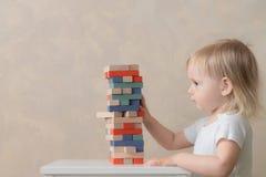 L'enfant pr?scolaire construit une tour des blocs en bois d?veloppement et ?ducation Concept du ` s d'enfants photos libres de droits