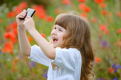 L'enfant prend la photo avec l'appareil-photo de téléphone portable extérieur en nature Photos libres de droits
