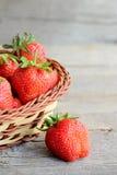 L'enfant prend une fraise d'un panier Le petit enfant juge une fraise disponible Badine la nourriture saine Fraises rouges juteus Images stock