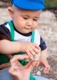 L'enfant prend une pierre de main de mère Images libres de droits