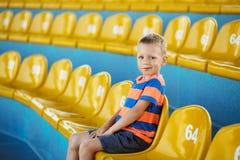 L'enfant prennent pour posséder le siège dans le stade ou le dolphinarium image stock