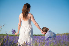 L'enfant a pressé sa tête à sa main du ` s de mère avec amour Image libre de droits