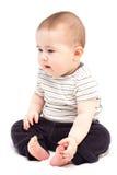 L'enfant réfléchi s'assied et regarde de côté Images stock