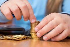 L'enfant rassemble la pile de pièces de monnaie d'or, plan rapproché Image stock
