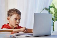 L'enfant recherche l'information sur l'Internet par un ordinateur portable auto-étude à la maison, faisant le travail Attentiveme photo stock