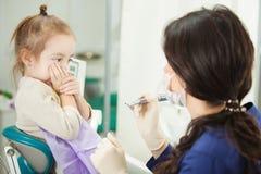 L'enfant refuse de passer par l'acte médical dans le bureau de dentiste image libre de droits