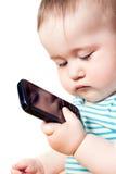 L'enfant regarde le téléphone et la pensée Images stock