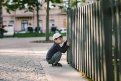 L'enfant regarde par le trou dans la barrière Images libres de droits