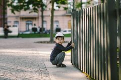 L'enfant regarde par le trou dans la barrière Photos stock