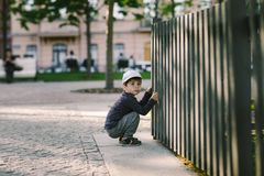 L'enfant regarde par le trou dans la barrière Photos libres de droits