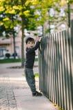 L'enfant regarde par le trou dans la barrière Images stock