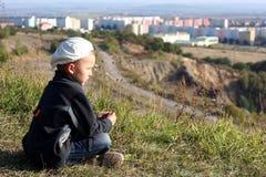 L'enfant regarde sur la ville des altitudes Photos stock