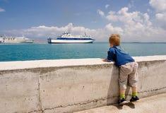 L'enfant regarde sur le bateau Image libre de droits