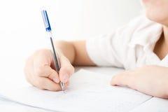 L'enfant remet écrire des devoirs photographie stock