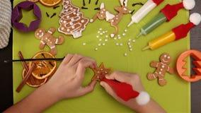 L'enfant remet décorer un biscuit en forme d'étoile de Noël de pain d'épice banque de vidéos