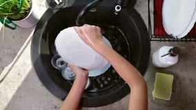 L'enfant remet laver un plat - vue supérieure banque de vidéos