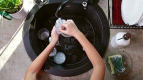 L'enfant remet laver un verre - vue supérieure banque de vidéos