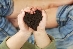 Mains d'enfant tenant le sol dans la forme de coeur Images stock