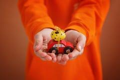 L'enfant remet tenir l'oeuf de pâques sur la voiture sur le fond orange Concept de vacances image libre de droits