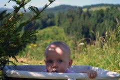 L'enfant riant se cache dans un panier en osier photographie stock