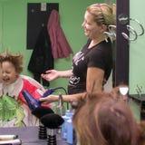 L'enfant sèche les cheveux dans un salon de coiffure photo stock