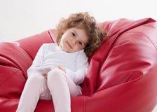 L'enfant s'asseyant sur les meubles encadrent moins images stock