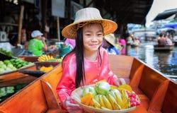 L'enfant s'asseyent sur le bateau et tiennent la corbeille de fruits Images stock