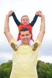 L'enfant s'assied au père sur des épaules avec la main soulevée Image libre de droits