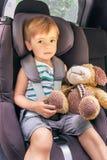 L'enfant s'assied dans le siège de voiture de sécurité Photographie stock libre de droits