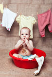 L'enfant s'assied dans un bassin photographie stock