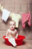 L'enfant s'assied dans un bassin Image stock