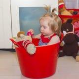 L'enfant s'assied dans un panier Une petite fille donne une tétine à a image stock