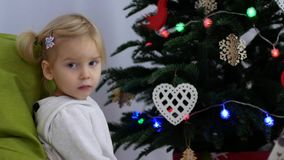 L'enfant s'assied près de l'arbre de Noël L'enfant attend le cadeau banque de vidéos