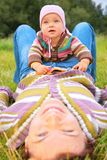 L'enfant s'assied sur la mère, qui se trouve sur l'herbe Photo libre de droits