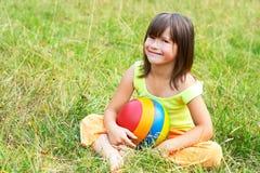 L'enfant s'assied sur une herbe image stock