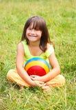 L'enfant s'assied sur une herbe photo stock