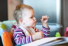 L'enfant s'assied une chaise d'arbitre et en tenant une cuillère dans sa bouche Image libre de droits
