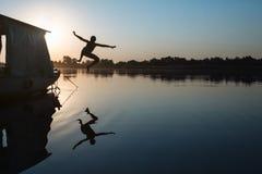 L'enfant sautant dans l'eau Photos stock