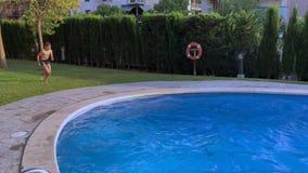 L'enfant sautant dans l'eau bleue de la piscine clips vidéos