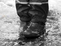 L'enfant sautant pour des magmas sur les routes dégèlent à la fin de l'hiver Image stock
