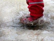 L'enfant sautant pour des magmas sur les routes dégèlent à la fin de l'hiver Image libre de droits