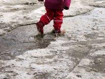 L'enfant sautant pour des magmas sur les routes dégèlent à la fin de l'hiver Photos libres de droits