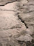 L'enfant sautant pour des magmas sur les routes dégèlent à la fin de l'hiver photo stock