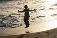 L'enfant sautant sur la plage Images libres de droits