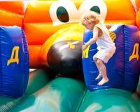L'enfant sautant sur le château plein d'entrain Image libre de droits