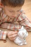 L'enfant sauvegardent des pièces de monnaie Photos stock