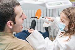 L'enfant scelle des dents à un mâle adulte images stock
